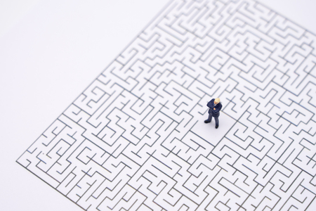 Miniature people businessmen standing in the center of the maze. Business Idea Concepts Troubleshooting Analysis of problems to find solutions. 스톡 콘텐츠