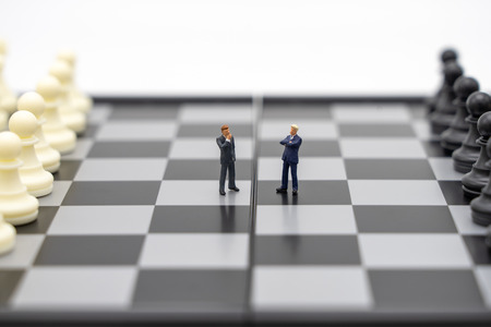 Miniature people businessmen standing on a chessboard with a chess piece on the back Negotiating in business. as background business concept and strategy concept with copy space. Imagens