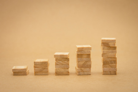 stack of wood businessmen standing Investment Analysis Or investment. The concept of being the number one business in the world stands at its peak.