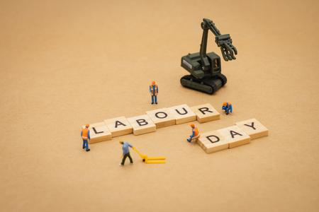 Miniaturleute, die mit Holzwort Tag der Arbeit als Hintergrund stehen Universal-Tageskonzept und Gesundheitstag-Konzept mit Kopienraum für Ihren Text oder Ihr Design. Standard-Bild