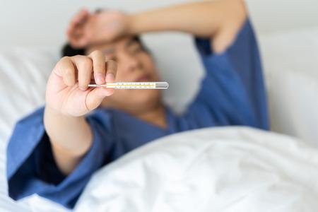 Hombre guapo asiático La hipotermia se ha medido por la fiebre. Acuéstese en la cama para darle un cuerpo de rehabilitación. El concepto de atención médica a los pacientes en casa por ti mismo.