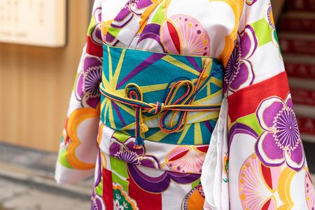 Jong meisje die Japanse kimono dragen die zich voor Sensoji-Tempel in Tokyo, Japan bevinden. Kimono is een traditioneel Japans kledingstuk. Het woord