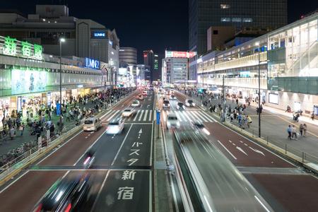 Auto's en voetgangers lopen op straatscène van verkeer bij de kruising van het Shinjuku-station in Tokio