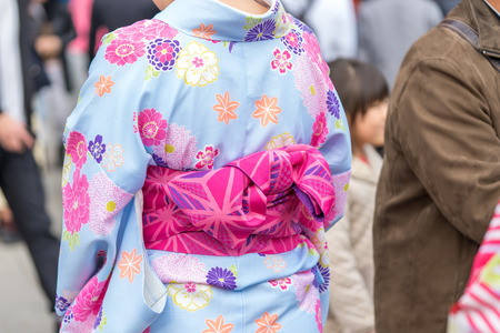 Young girl wearing Japanese kimono standing in front of Sensoji Temple in Tokyo, Japan. Kimono is a Japanese traditional garment. The word Zdjęcie Seryjne