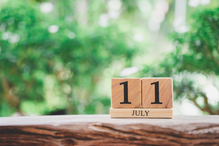 July 11  wooden calendar on vintage wood abstract background. world population day  with copy space for your text.