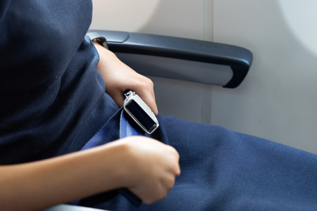 Passengers on the plane expecting belts for safety while traveling. The concept of travel Travel safety