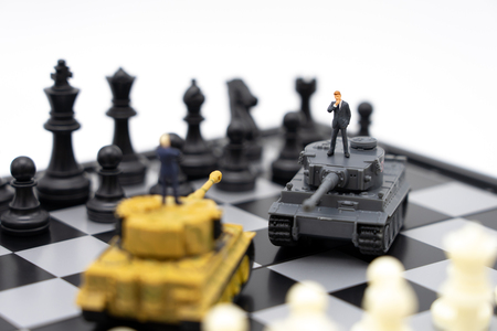 Miniature people businessmen standing on a chessboard with a Tank model on the back Negotiating in business. as background revolution concept and strategy concept with copy space.