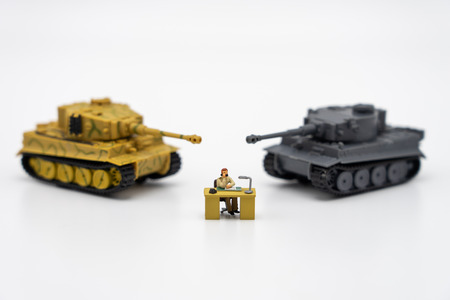Miniature people businessmen sitting on a chessboard with a Tank model on the back Negotiating in business. as background revolution concept and strategy concept with copy space.