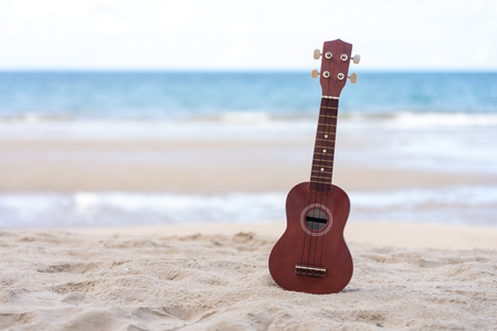 guitar ukulele put on the sand beach. Sea view during daytime with blue sky background. Summer season concept. 写真素材