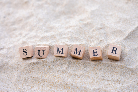 Summer word written on wooden block put on the sand beach. Sea view during daytime with blue sky background. Summer season concept. 写真素材 - 124722582