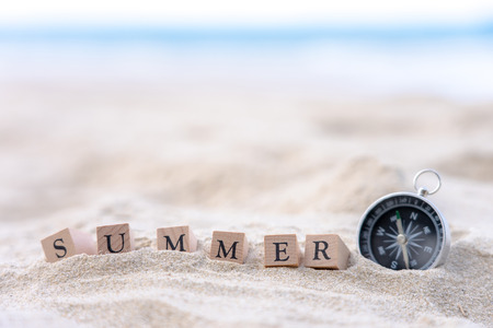 Summer word written on wooden block put on the sand beach. Sea view during daytime with blue sky background. Summer season concept.