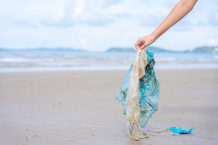 Woman's hand picking up used plastic bag on sand beach, cleaning seaside beach.  Environmental pollution, Ecological problem and  Marine pollution concept. 写真素材 - 124722587