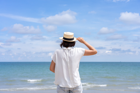 Outdoor summer portrait of Young Asian woman wearing stylish hat and clothes standing on the beach, enjoying looking view of sea with blue sky on summer vacation. 写真素材 - 124722588