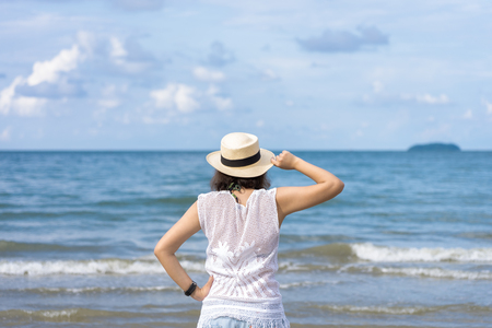 Outdoor summer portrait of Young Asian woman wearing stylish hat and clothes standing on the beach, enjoying looking view of sea with blue sky on summer vacation. 写真素材