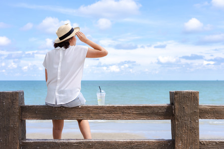 Outdoor summer portrait of Young Asian woman wearing stylish hat and clothes sitting on the bars, enjoying looking view of sea with blue sky on summer vacation. 写真素材 - 124722594