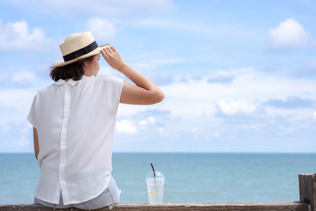 Outdoor summer portrait of Young Asian woman wearing stylish hat and clothes sitting on the bars, enjoying looking view of sea with blue sky on summer vacation.