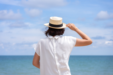 Outdoor summer portrait of Young Asian woman wearing stylish hat and clothes standing on the beach, enjoying looking view of sea with blue sky on summer vacation. 写真素材 - 124722596