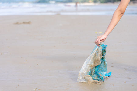 Woman's hand picking up used plastic bag on sand beach, cleaning seaside beach.  Environmental pollution, Ecological problem and  Marine pollution concept. 写真素材 - 124722543