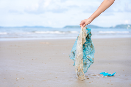 Woman's hand picking up used plastic bag on sand beach, cleaning seaside beach.  Environmental pollution, Ecological problem and  Marine pollution concept.