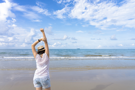 Outdoor summer portrait of Young Asian woman wearing stylish hat and clothes standing on the beach, enjoying looking view of sea with blue sky on summer vacation. 写真素材 - 124722548