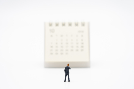 Miniature people businessmen standing on white calendar using as background business concept and finance concept with copy space  for your text or  design.