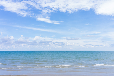 Yellow warm sand and summer sea with blue sky and copy space. Sea view during daytime with blue sky and white clouds. Summer season concept.