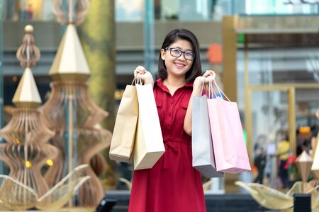 Beautiful girl holding a shopping bag. Many bags show a happy feeling. In the purchase. Shop at discount stores. The festival. Shopping concept Stok Fotoğraf
