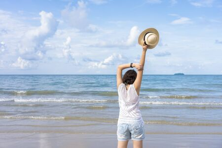 Outdoor summer portrait of Young Asian woman wearing stylish hat and clothes standing on the beach, enjoying looking view of sea with blue sky on summer vacation. 版權商用圖片