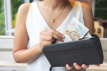 Asiatische Frauen holen thailändische Banknoten aus der Handtasche, um Essen oder Dienstleistungen zu bezahlen. Zahlungskonzept, Service
