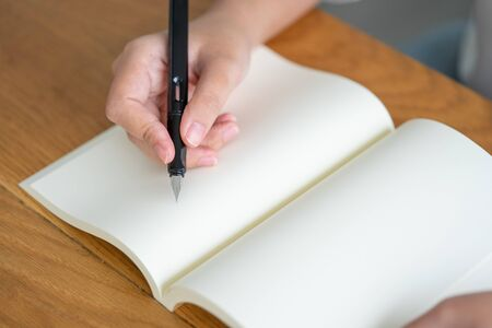 Asian girl holding a black pen writing into an empty book. Diary writing stories recorded impressive. Memories on a wooden table