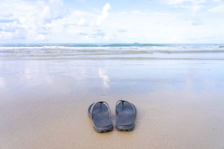 Shoes were placed on the beach by the sea, reflecting the sky. Giving the feeling of rest, leave from long work Summer concept Long vacation 写真素材