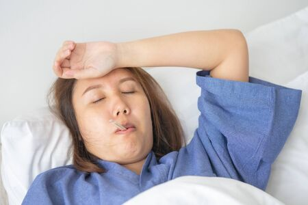 Asian Beautiful Woman Hypothermia has been measured by fever. Lie on the bed to give a body of rehabilitation. The concept of medical care to patients at home by yourself.