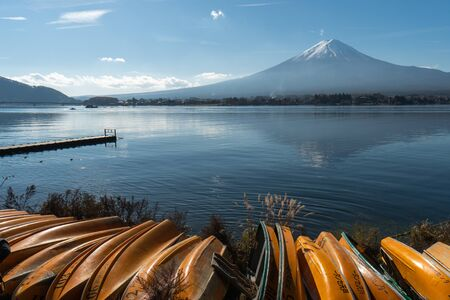 Landscape of view the Mount Fuji and Lake Kawaguchiko In the morning is a tourist attraction of Japan. In a small town There is a yellow fishing boat on the lake. Stock Photo