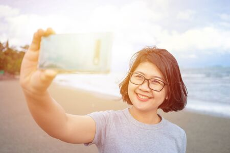 Beautiful young woman holding a smartphone. In order to take a picture of yourself from a camera phone (Selfie). Tourism concept alone Self-portrait photography 写真素材