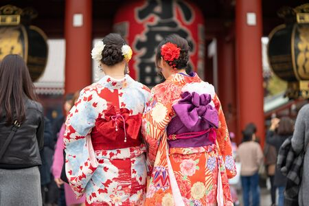 Young girl wearing Japanese kimono standing in front of Sensoji Temple in Tokyo, Japan. Kimono is a Japanese traditional garment. The word Banque d'images - 128616672