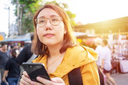 Portrait Schöne asiatische Frauen stehen auf dem Chatuchak-Markt in Thailand, um Smartphones zu halten. Bangkok ist eine Touristenattraktion für Ausländer.