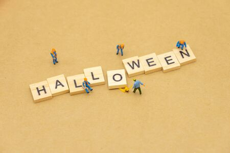 Miniature people standing with wood word HALLOWEEN using as background Universal day concept and halloween Day concept with copy space  for your text or design.