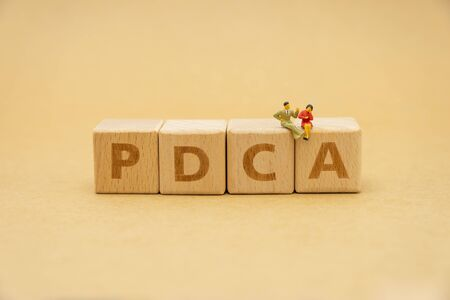 Miniature people sitting on wood word PDCA using as background business concept and Strategy concept with copy space for your text or design.