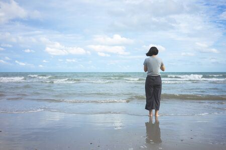 Asian young woman standing facing the sea. Feeling really lonely, heartbroken sea like a nursery of clearing the mind. The concept of liberation travel alone. 写真素材