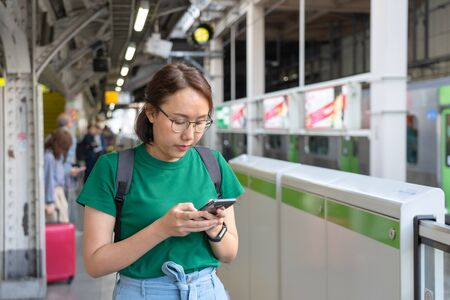 Asian girl Play smartphone For entertainment and work outside the office or outside. Out of Office Concepts Work wirelessly Communication in the modern world.