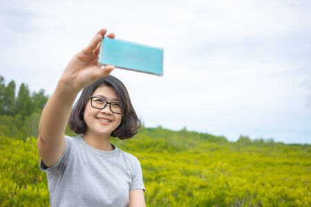 Beautiful young woman holding a smartphone. In order to take a picture of yourself from a camera phone (Selfie). Tourism concept alone Self-portrait photography Stock Photo
