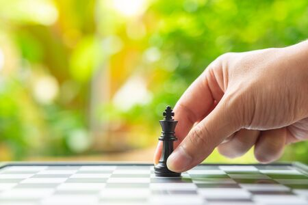 Businessman holding a King Chess is placed on a chessboard.using as background business concept and Strategy concept with copy space for your text or design.