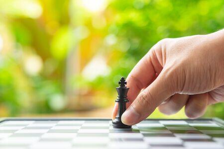 Homme d'affaires détenant un roi d'échecs est placé sur un échiquier.utilisant comme concept d'entreprise d'arrière-plan et concept de stratégie avec espace de copie pour votre texte ou votre conception. Banque d'images