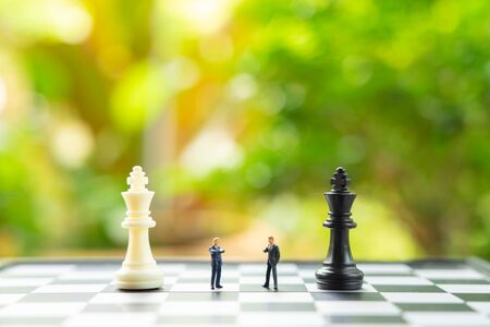 Miniature people businessmen standing on a chessboard with a chess piece on the back Negotiating in business. as background business concept and strategy concept with copy space. Stockfoto