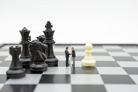 Miniatur 2-Personen-Geschäftsleute Händeschütteln stehend auf einem Schachbrett mit einer Schachfigur auf der Rückseite Verhandeln im Geschäft. als Hintergrundgeschäftskonzept und Strategiekonzept mit Kopienraum.