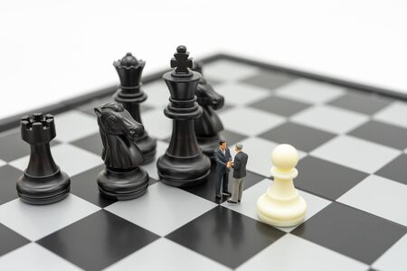 Miniature 2 people businessmen Shake hands standing on a chessboard with a chess piece on the back Negotiating in business. as background business concept and strategy concept with copy space.