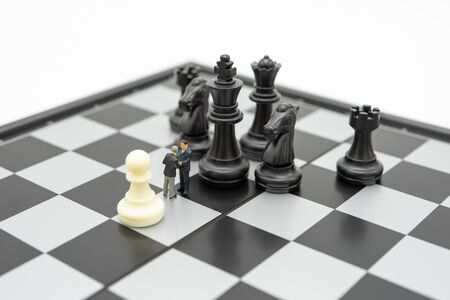 Miniature 2 people businessmen Shake hands standing on a chessboard with a chess piece on the back Negotiating in business. as background business concept and strategy concept with copy space. Stockfoto