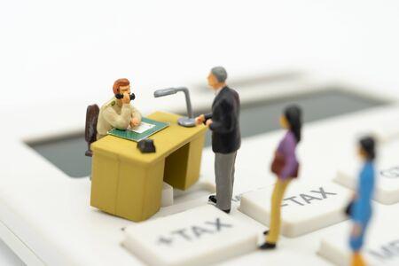 Personas en miniatura Cola de pago Ingresos anuales (IMPUESTOS) del año en la calculadora. utilizando como fondo el concepto de negocio y el concepto de finanzas con espacio de copia para su texto o diseño.