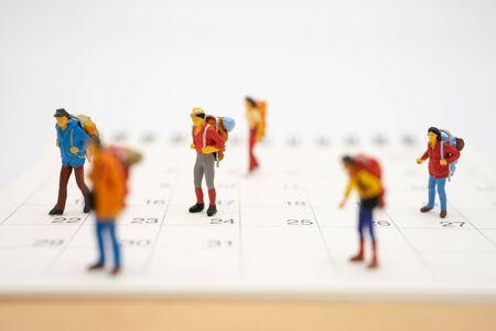 Le persone in miniatura stanno sulla passerella l'inizio del viaggio Per raggiungere la meta. utilizzando come concetto di viaggio di sfondo con spazi di copia per il tuo Archivio Fotografico