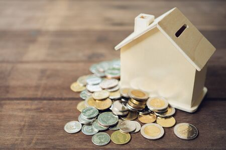 A model house model is placed on a pile of coins.using as background business concept and real estate concept with copy space for your text or design. 写真素材 - 130118523